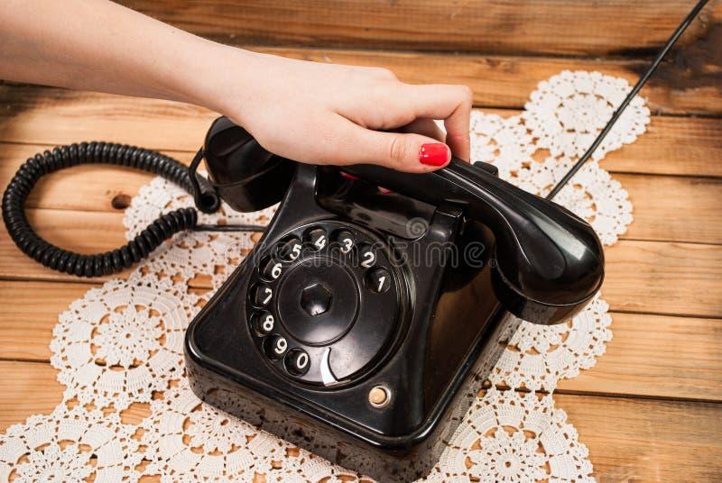 拿着在鞋带桌布和木背景的女孩手老电话耳机 免版税库存照片