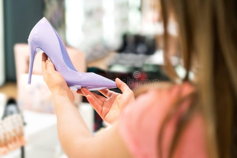 拿着在鞋店的妇女桃红色高跟鞋 免版税库存照片