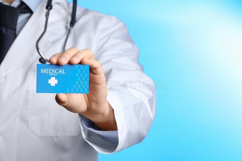 拿着在颜色背景的医生名片 医疗 免版税库存照片