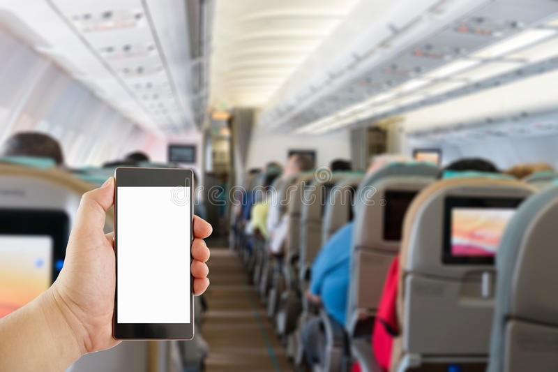 拿着在飞机内部的手手机 免版税库存照片