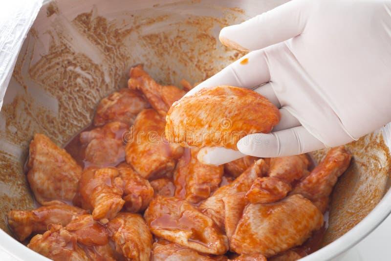 拿着在香料的手未加工的鸡翼为烹调做准备 库存照片