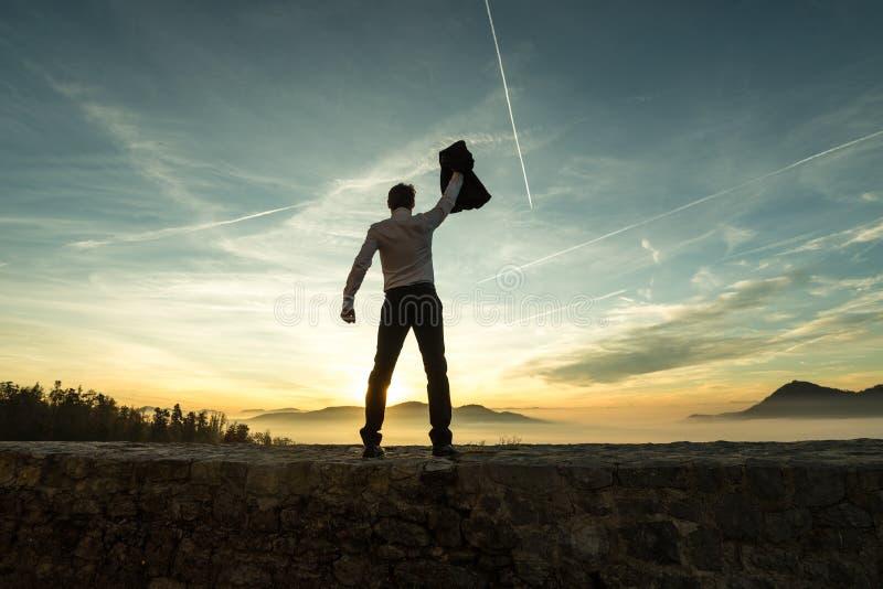 拿着在高处他的夹克的商人在日落 免版税库存照片