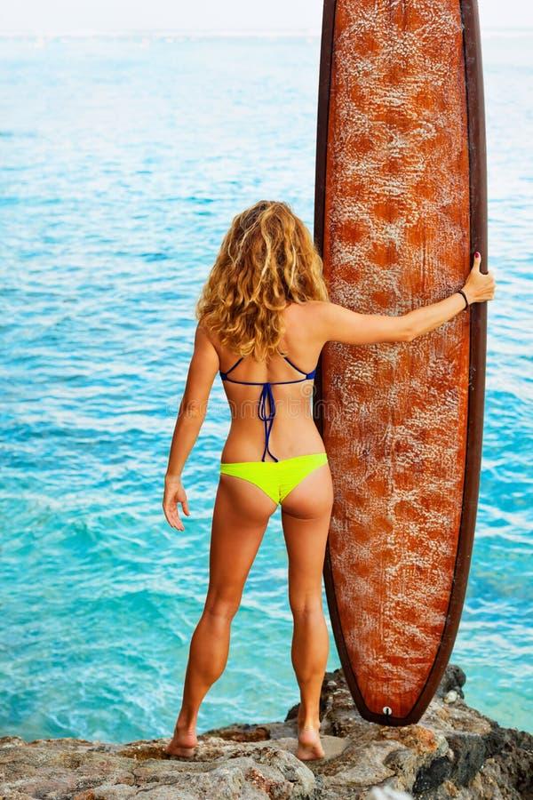 拿着在高峭壁的比基尼泳装的冲浪者女孩冲浪板立场 免版税库存照片