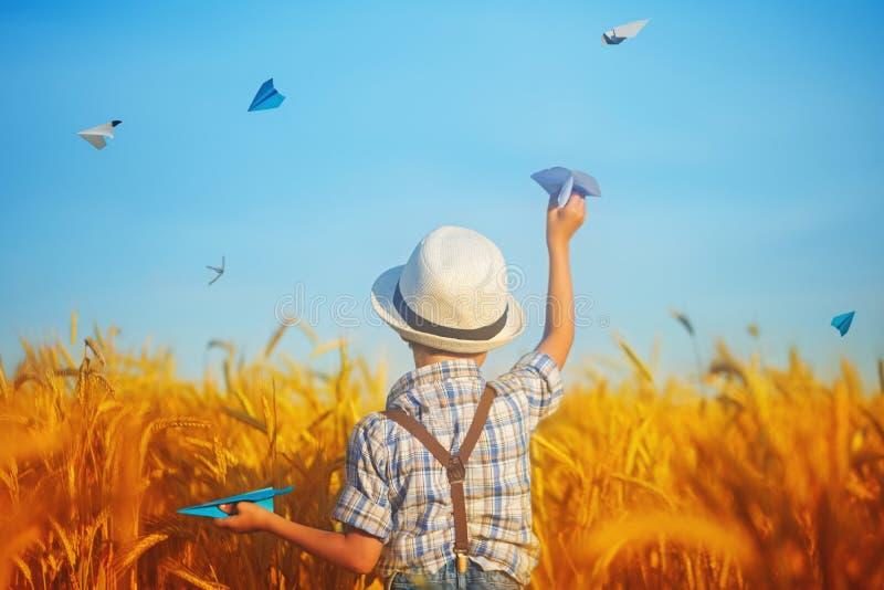 拿着在麦子金黄领域的逗人喜爱的孩子手中纸飞机在一个晴朗的夏日 免版税库存照片