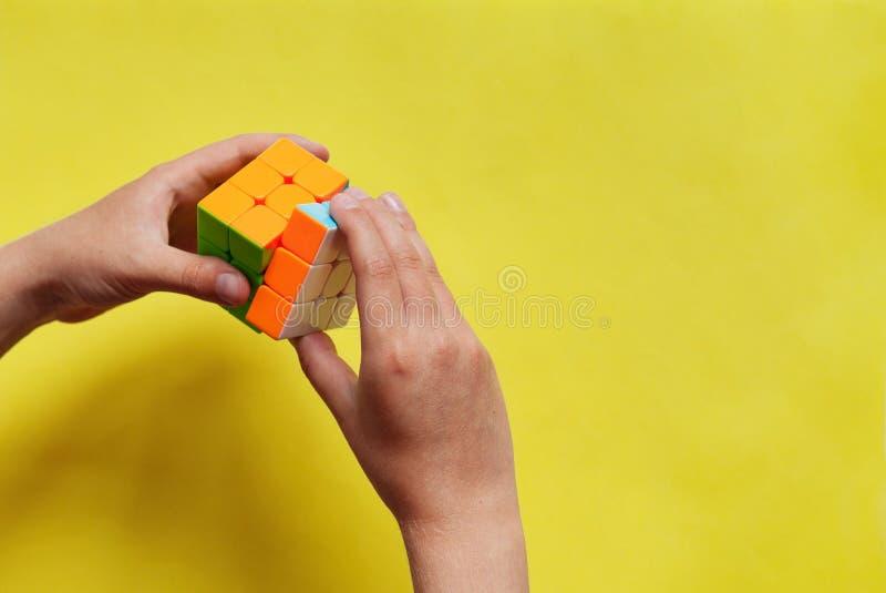 拿着在黄色背景的儿童手五颜六色的Rubik的立方体 戏剧比赛和难题建筑的概念 特写镜头,顶视图 免版税库存照片