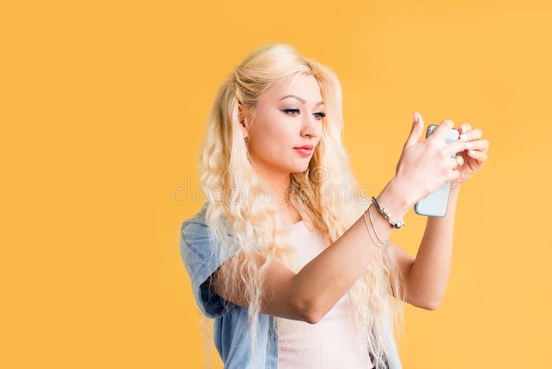 拿着在黄色背景的快乐的美丽的年轻女人照片手机 免版税库存图片