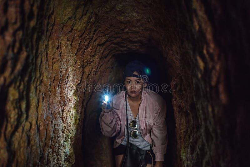 拿着在黑暗的老矿隧道的亚裔妇女火炬 免版税库存图片