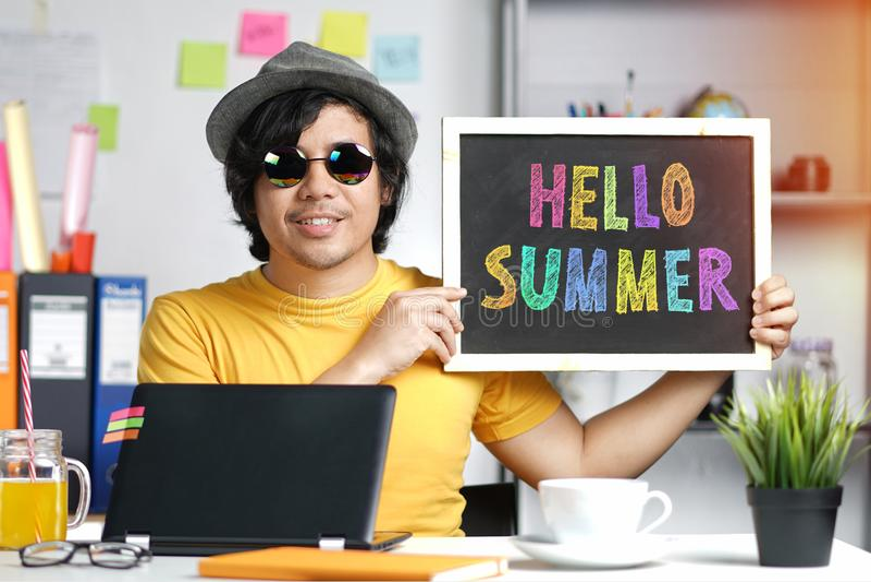 拿着在黑板的年轻人五颜六色的你好夏天文本,当时 库存照片