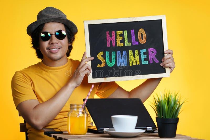 拿着在黑板的年轻人五颜六色的你好夏天文本,当时 图库摄影