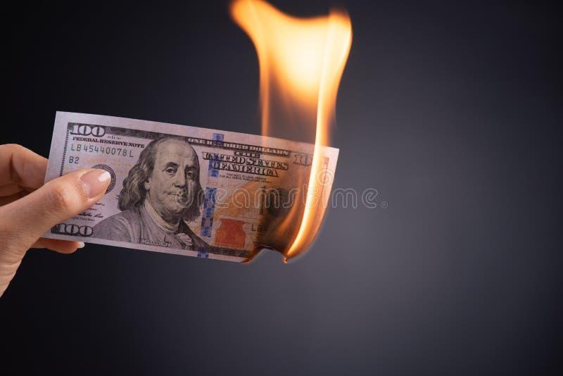 拿着在黑背景-企业财务、储款和破产概念的妇女手燃烧的灼烧的美元现金金钱 免版税库存照片