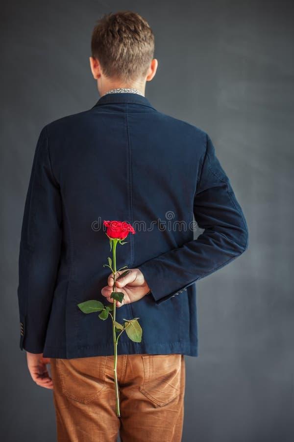拿着在他的后的年轻人背面图红色玫瑰  免版税图库摄影