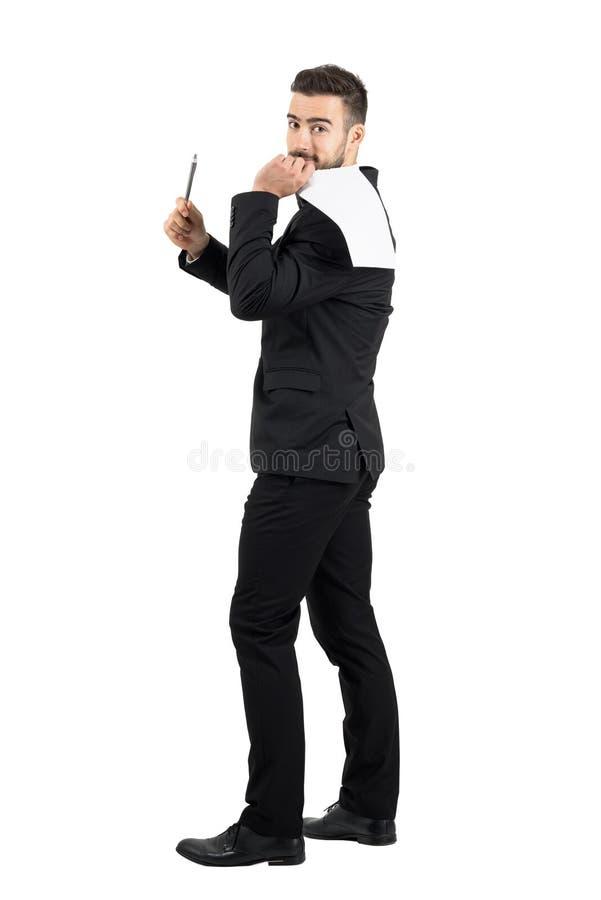 拿着在他的后面提供的笔的衣服的年轻商人合同纸署名的 免版税库存图片