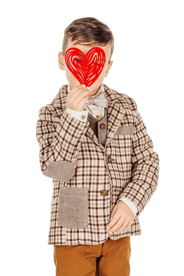 拿着在他的手上的微笑的男孩红色心脏隔绝在白色 图库摄影