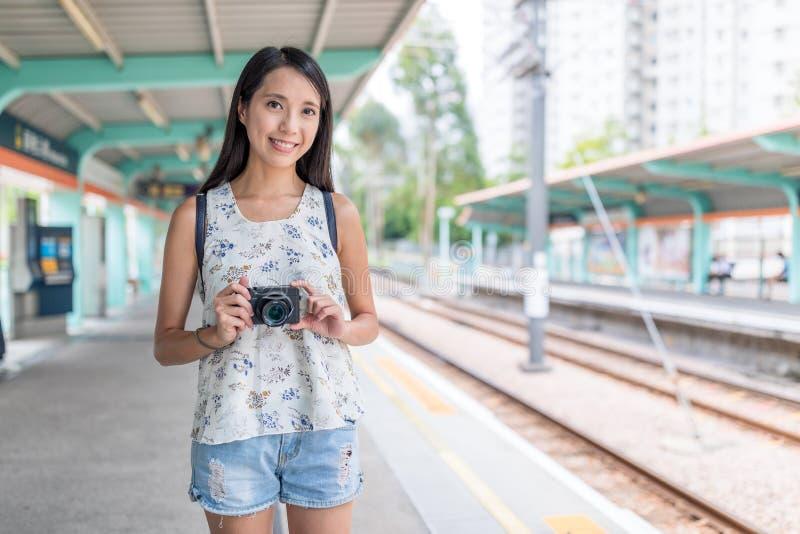 拿着在轻的火车站的年轻亚裔妇女数字照相机 库存图片