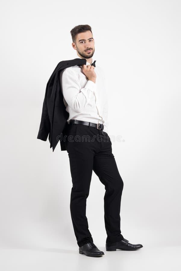 拿着在他的肩膀的典雅的人无尾礼服外套看照相机 免版税库存照片