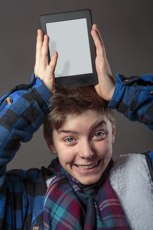 拿着在他的头的疯狂的男孩一台片剂计算机 图库摄影