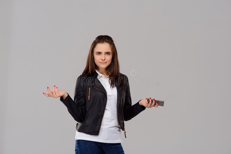 拿着在紫色背景的生气的年轻美丽的女孩电话 库存图片
