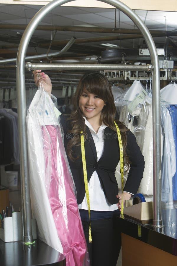 拿着在洗衣店的确信的所有者干净的礼服 免版税库存图片