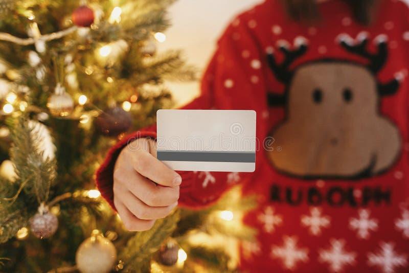 拿着在golde背景的美丽的少妇信用卡  免版税库存照片
