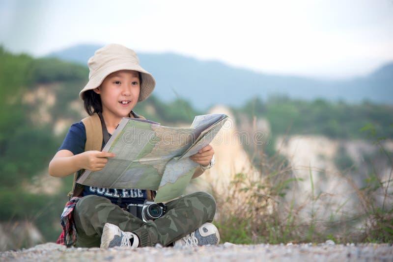拿着地图和旅行背包的儿童亚裔女孩站立在山 免版税库存图片