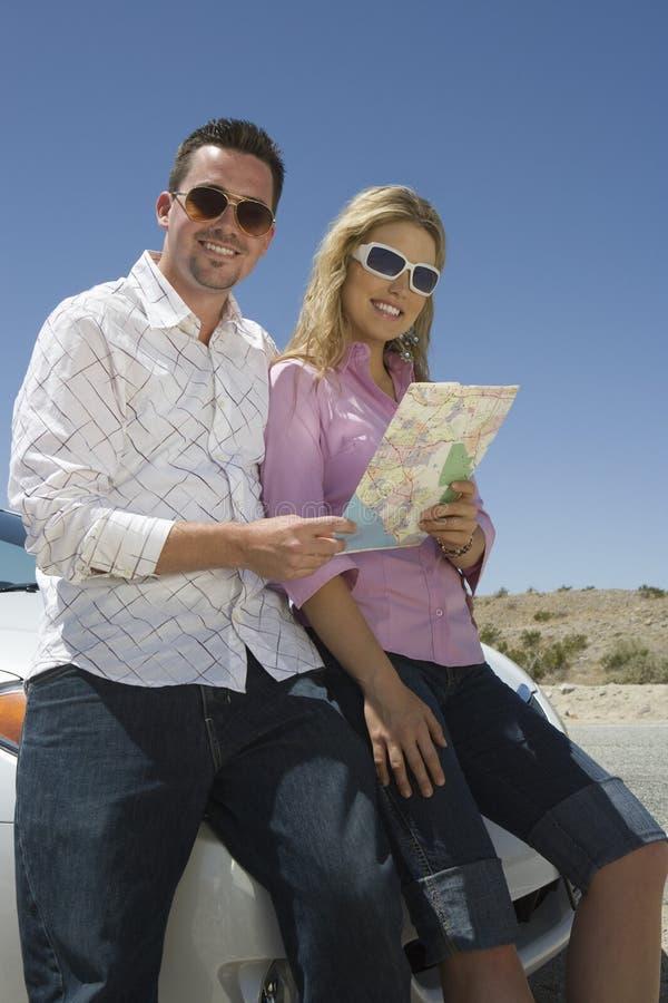 拿着地图的一对愉快的夫妇的画象 免版税库存照片