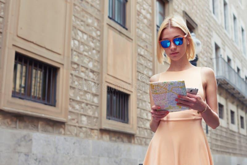 拿着地图的华美的妇女,当游览海外时 库存图片