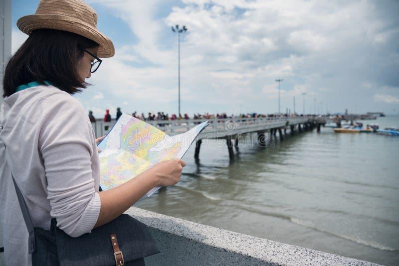 拿着地图的幸福年轻亚裔妇女 免版税图库摄影