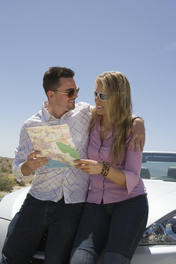 拿着地图的愉快的夫妇 免版税库存图片