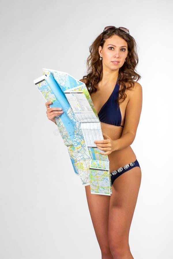 拿着地图的愉快的妇女-被隔绝在白色背景 库存照片