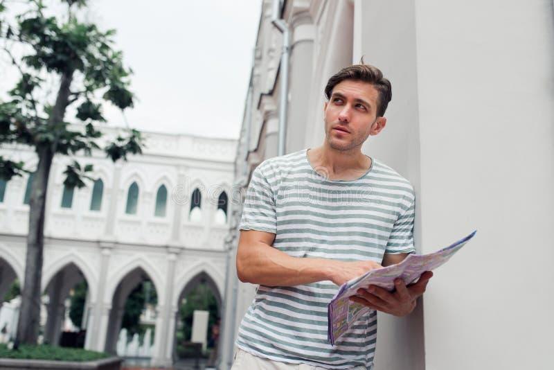拿着地图的年轻人,当游览外国城市时 库存图片