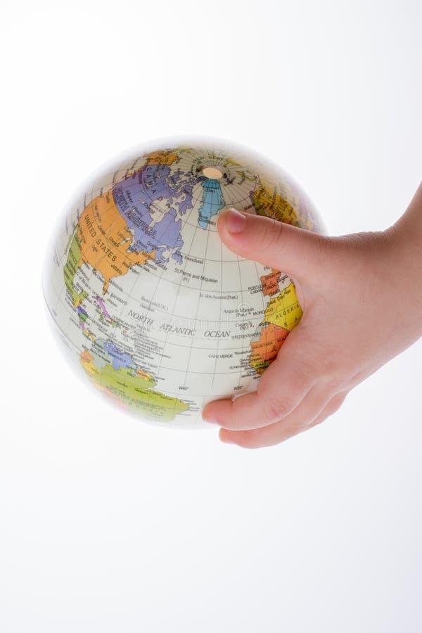 拿着地球和一支笔在他的手上的孩子 免版税库存照片