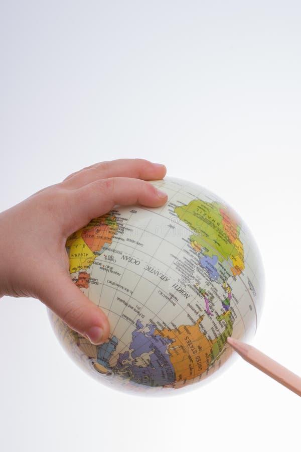 拿着地球和一支笔在他的手上的孩子 库存图片