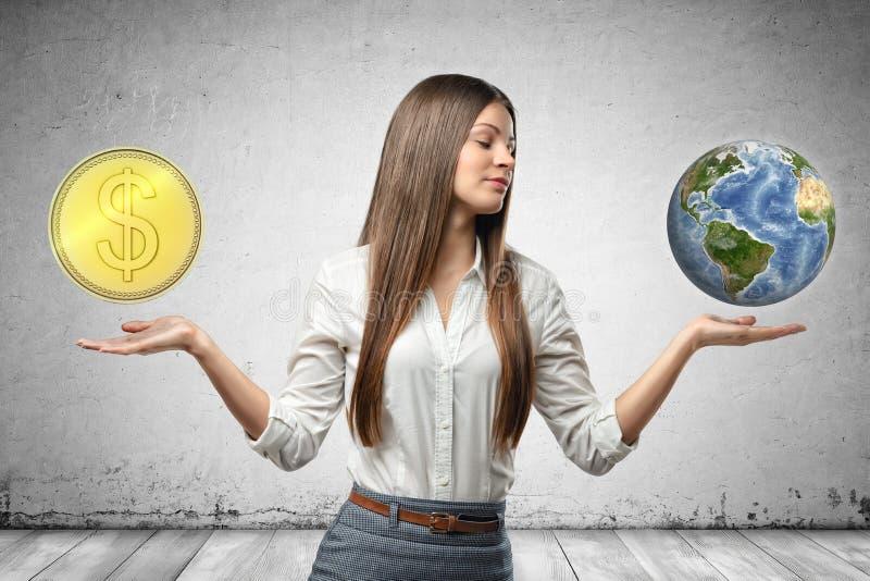 拿着地球地球和金黄美元硬币在她的手上的年轻女商人在灰色墙壁背景 免版税库存图片