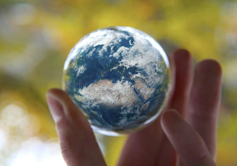 拿着地球有秋天背景的手 免版税图库摄影