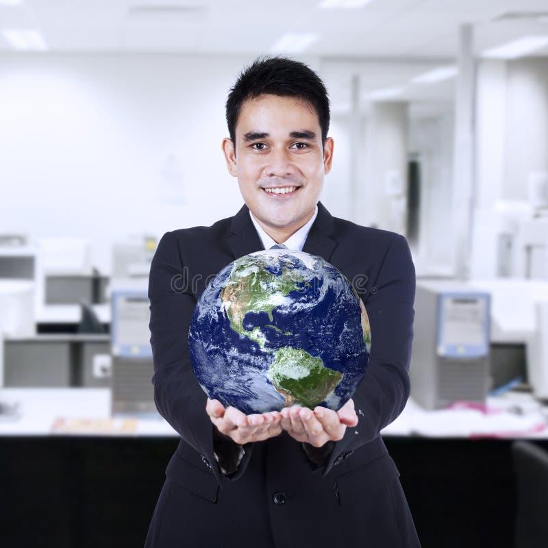 拿着地球的商人 免版税库存照片
