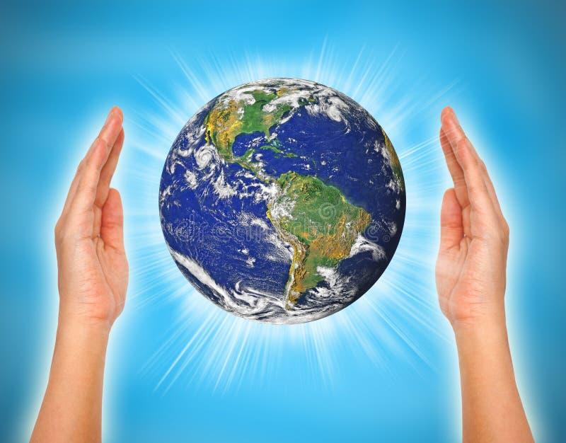拿着地球的妇女的手 皇族释放例证