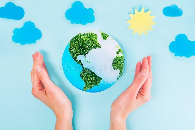 拿着地球纸和绿色新芽拼贴画的顶视图女性手在与纸太阳和云彩的蓝色背景塑造 在y的地球 库存图片