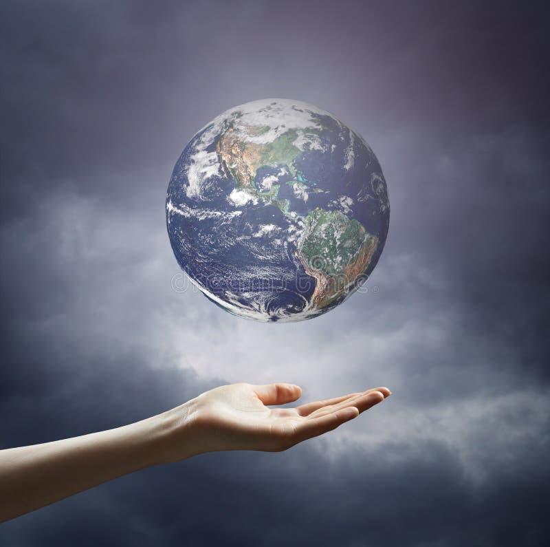 拿着地球行星的手的图象 免版税库存照片