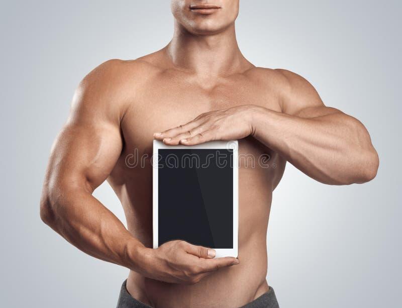 拿着垂直有黑屏的健身男性数字式片剂 库存照片