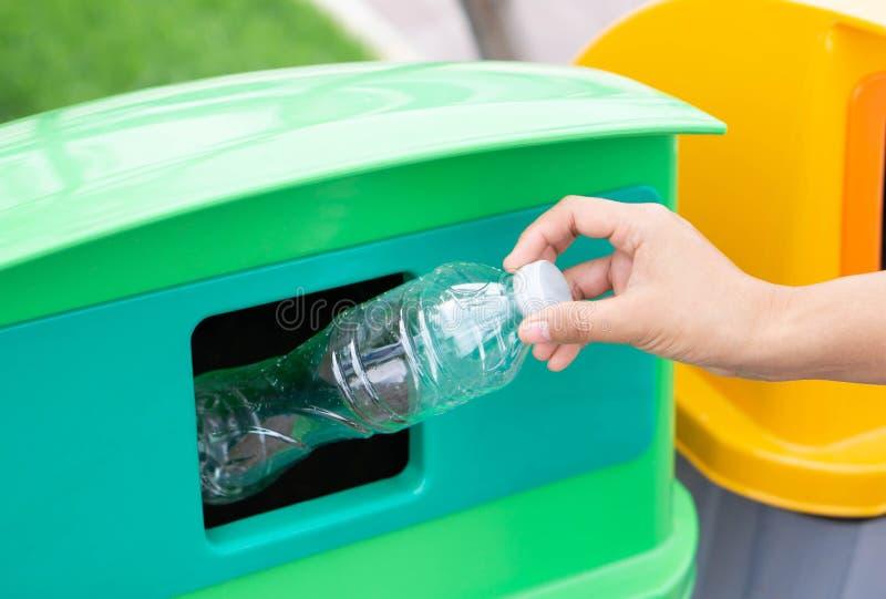 拿着垃圾塑料瓶的接近的手入回收垃圾桶,选择聚焦 库存照片