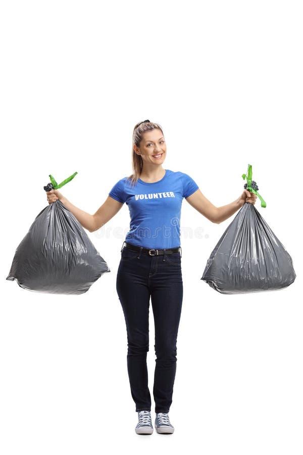 拿着垃圾塑料袋的年轻女性志愿者 免版税库存照片