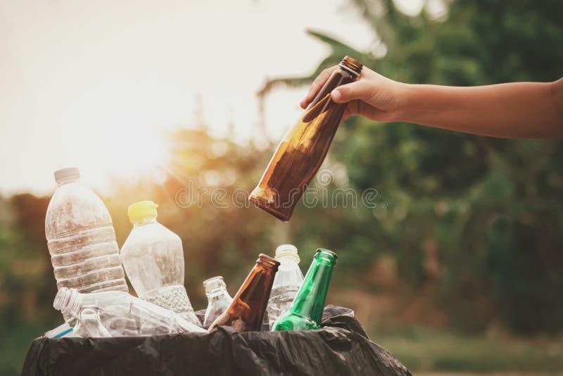 拿着垃圾玻璃瓶的手放入回收袋子 图库摄影