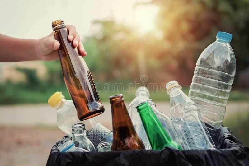 拿着垃圾玻璃瓶的手放入回收袋子 免版税库存图片