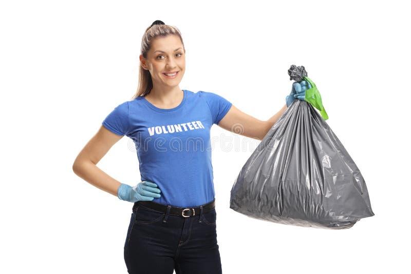 拿着垃圾袋的快乐的年轻女性志愿者 免版税库存照片