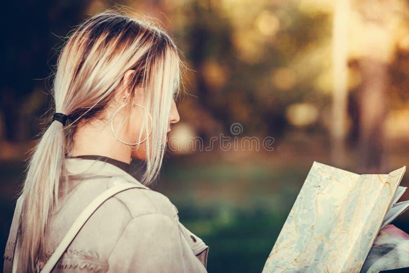 拿着城市地图的年轻失去的妇女,当站立时 免版税库存照片