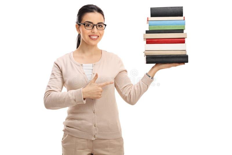 拿着堆书和指向的年轻女老师 库存图片