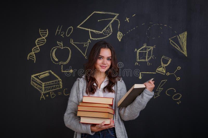 拿着堆书的女孩,坚持有想法的标志的一个委员会,科学和知识 免版税库存图片
