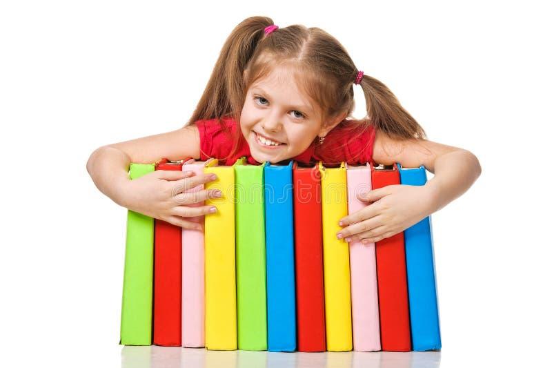 拿着堆书的小女孩。 隔绝。 免版税库存照片