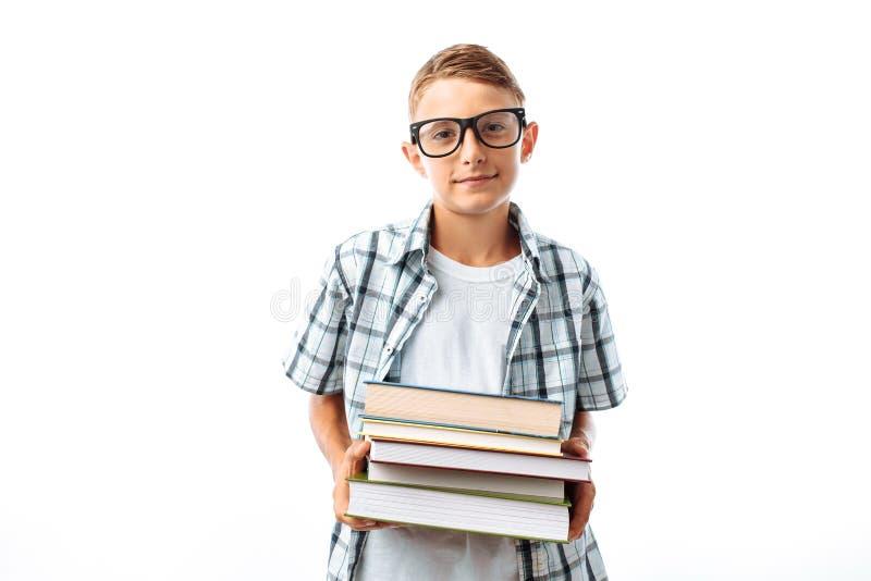 拿着堆书的美丽的学生,植物学家去与书在白色背景的演播室学习 图库摄影