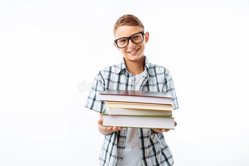拿着堆书的美丽的学生,植物学家去与书在白色背景的演播室学习 免版税库存照片